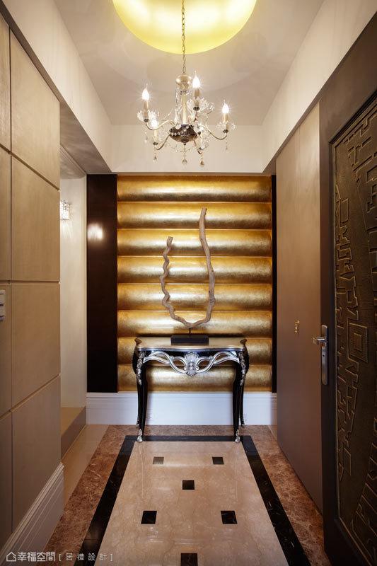 甫進玄關,大器磅礡的意象映入眼前,端景牆以金銅色的弧形波紋呈現,地坪則以拼接大理石來揮灑氣韻,將異質材的表現發揮盡致。