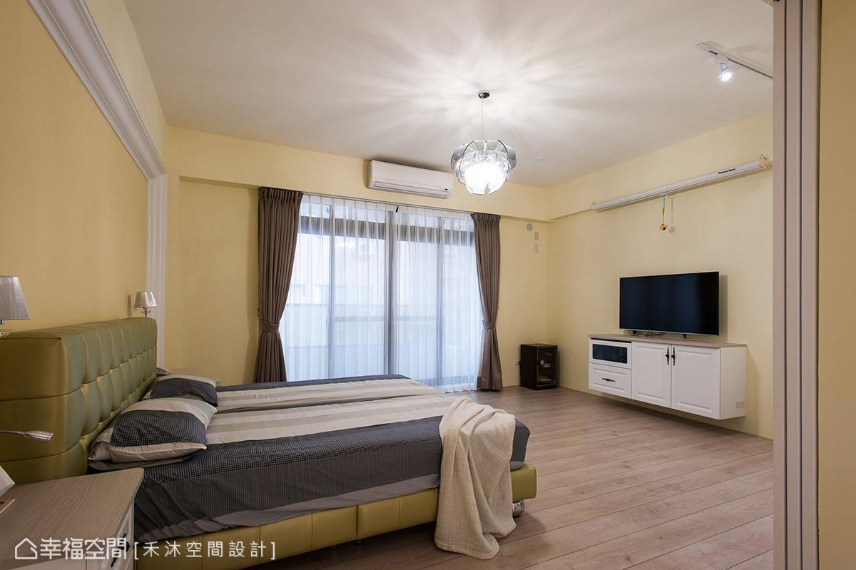 簡約乾淨的主臥房以鵝黃色調帶入溫暖氛圍,並運用美式線板簡單勾勒出床頭主牆氣勢。