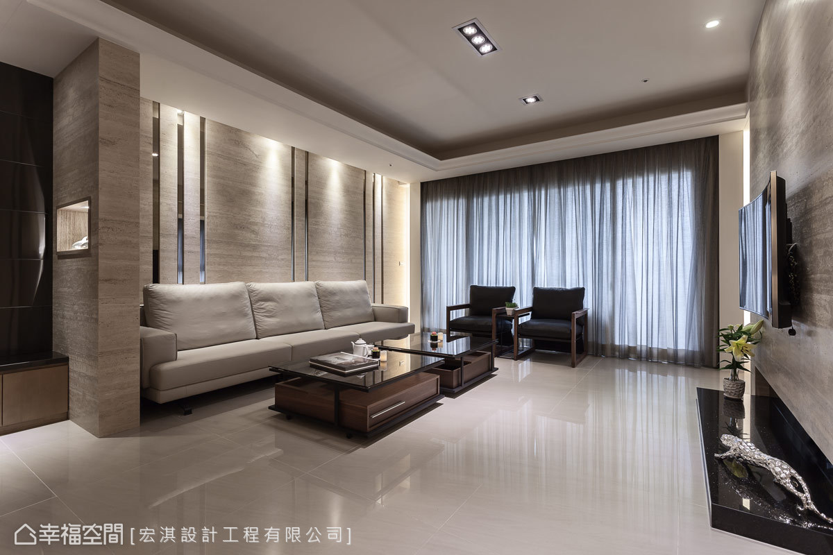 沙發背牆以天然洞石為底,並佐上茶鏡的線條勾勒,在燈光的映照之下,展現複合性材質的交融之美。