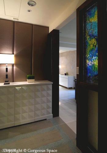 白色素雅的端景櫃,其中一部分設計為可拉出使用的穿鞋椅。編織背板以及如潑墨雲彩般的融雕玻璃,讓玄關場域顯得氣質出眾。