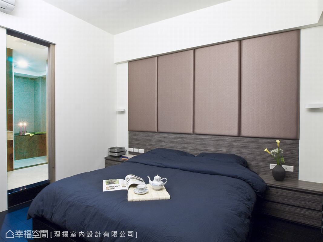 主牆以木作及裱布的創意手法,形塑出空間的視覺焦點,拉直床頭主牆部份,將樑下整合成為收納的使用機能,掩去床頭壓樑的風水問題。