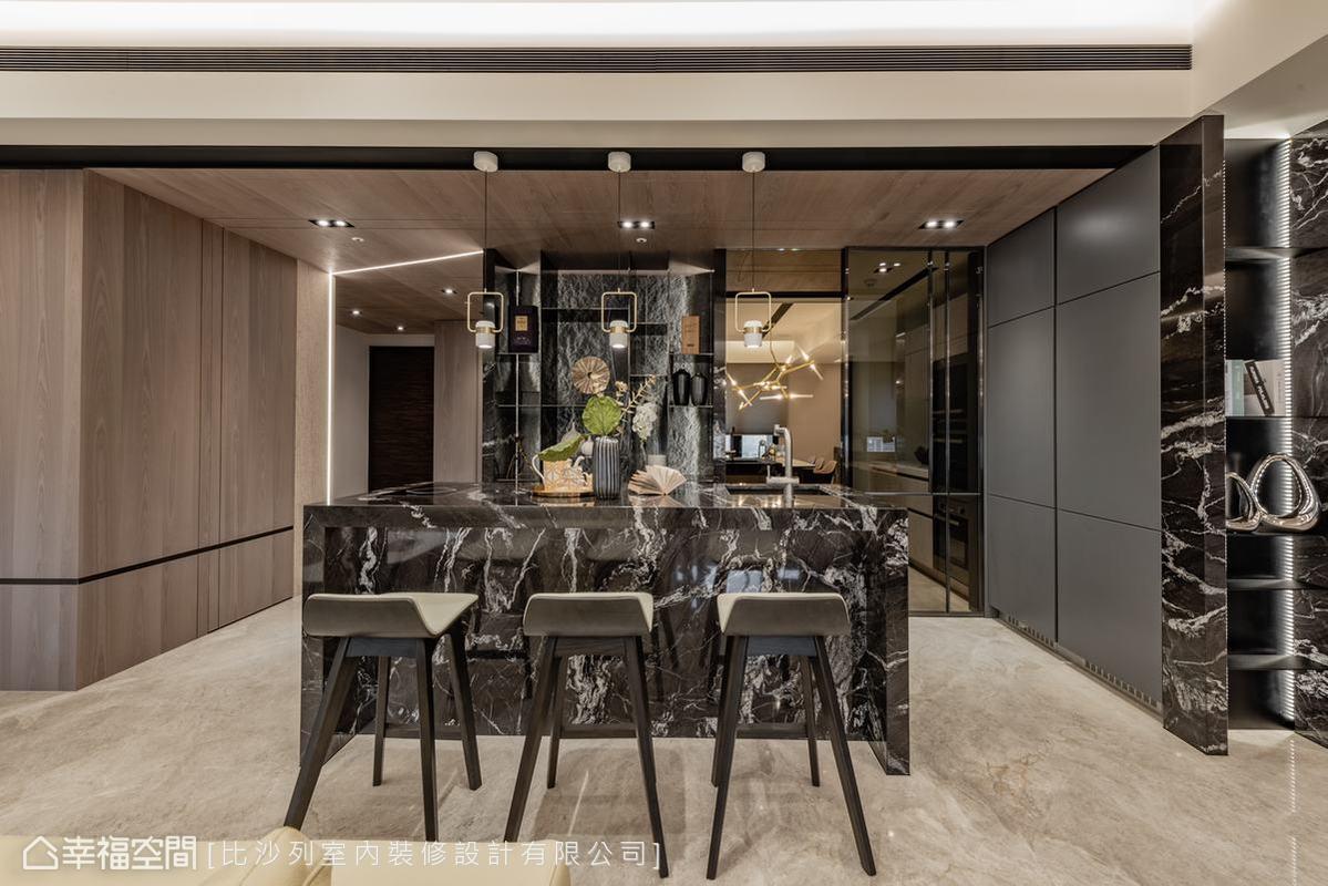 與客廳毗鄰的吧檯區利用黑色大理石營造出一種低調奢華與沉邃的韻味,有效定義出此分區。