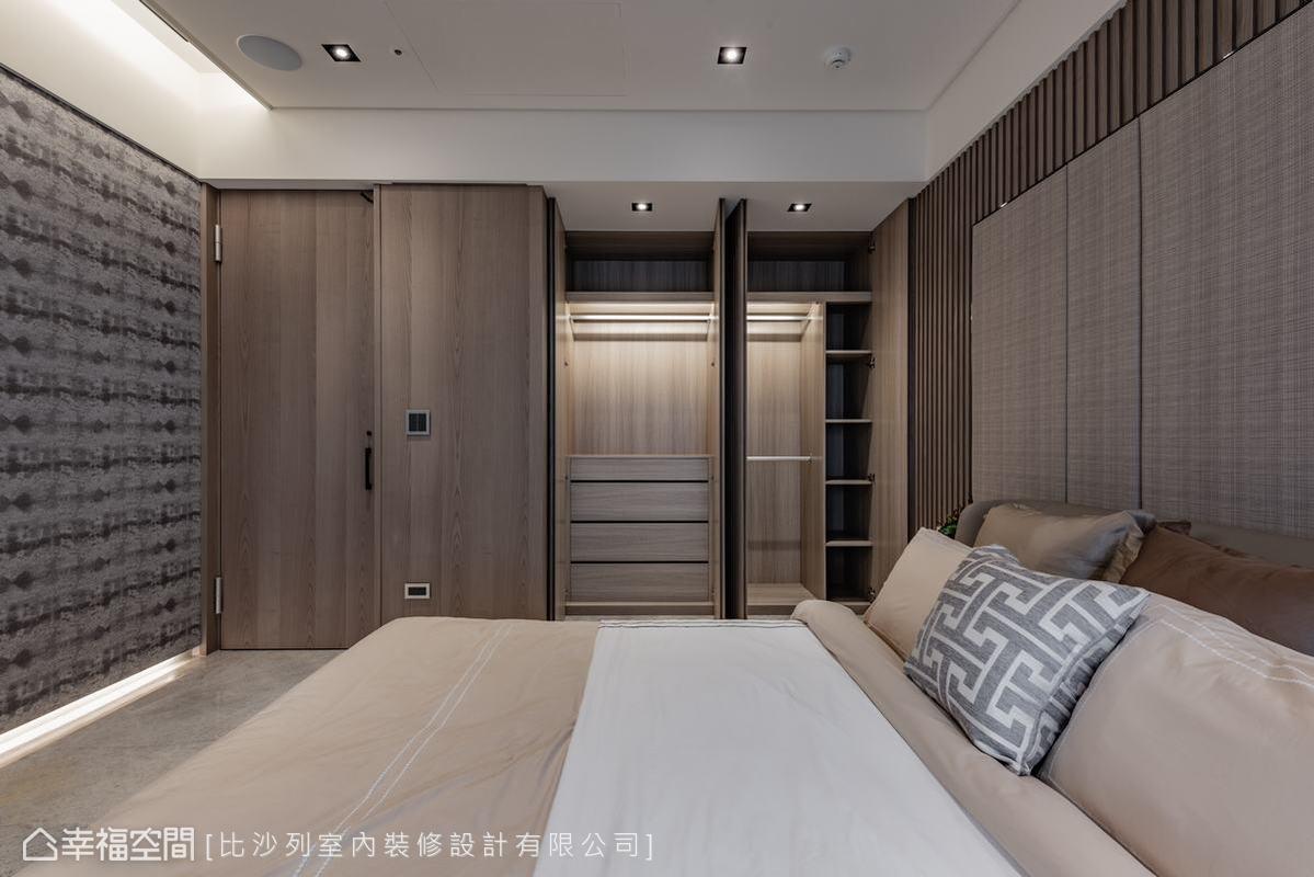 隨著隱藏式門片拉開,充裕的收納空間驀然而現,運用統一的木質材質鋪陳的設計手法讓空間畫面顯得乾淨。