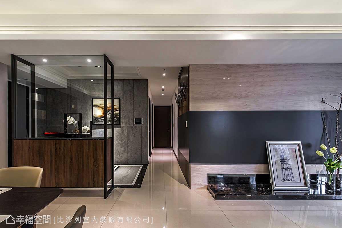 玄關與餐廳之間,以鐵件框架結合上半高腰櫃,零界線手法巧妙將玄關坪效融於大公領域之內。