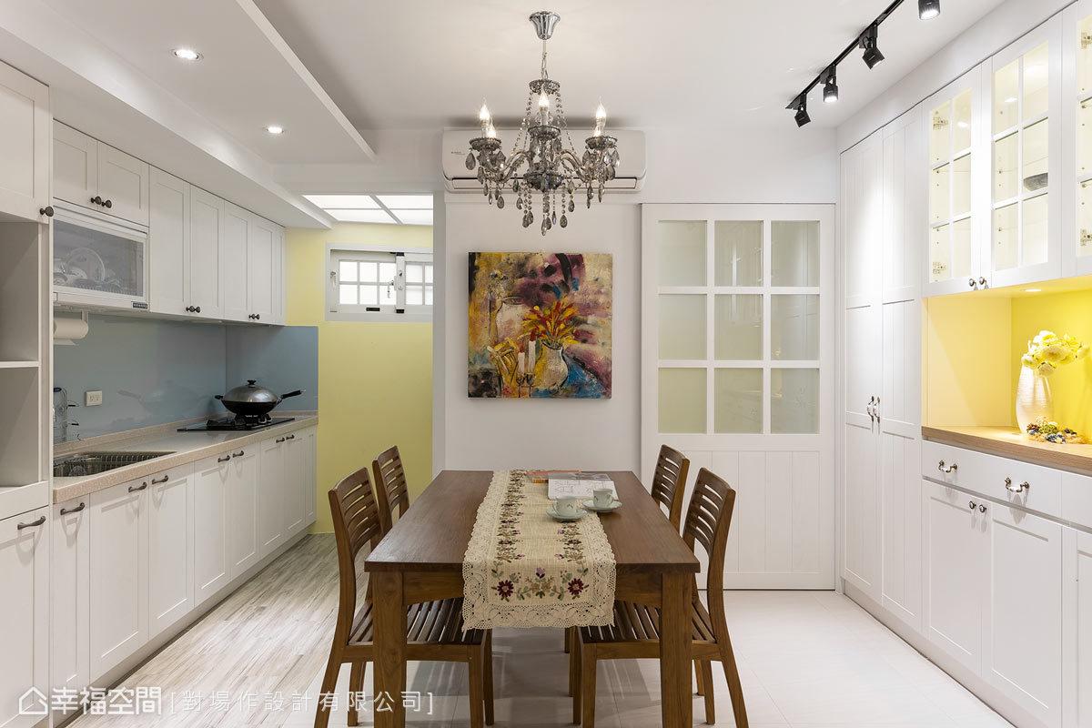 廚具造型選擇鄉村風的板材,淡藍色的烤漆玻璃搭配對面的鵝黃色牆面,讓整體視覺更加俐落清爽。地坪則挑選木紋磚的材質,與餐廳的拋光石英磚作界線。