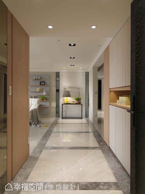 地坪以切割大理石構成長廊,並設置端景櫃締造迎賓意象,同時也利用兩側做足收納,一邊櫃面處理成鏡面,有放大空間的效果,另一邊做成暗櫃造型收納。