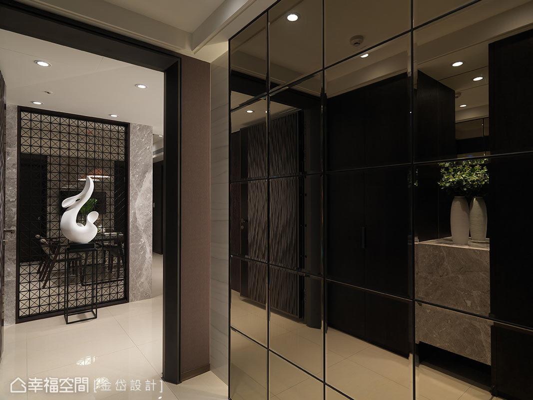 推開門扉,玄關區右側以茶鏡櫃面處理,有放大空間之效,前方造型屏風則形塑豪邸意象。