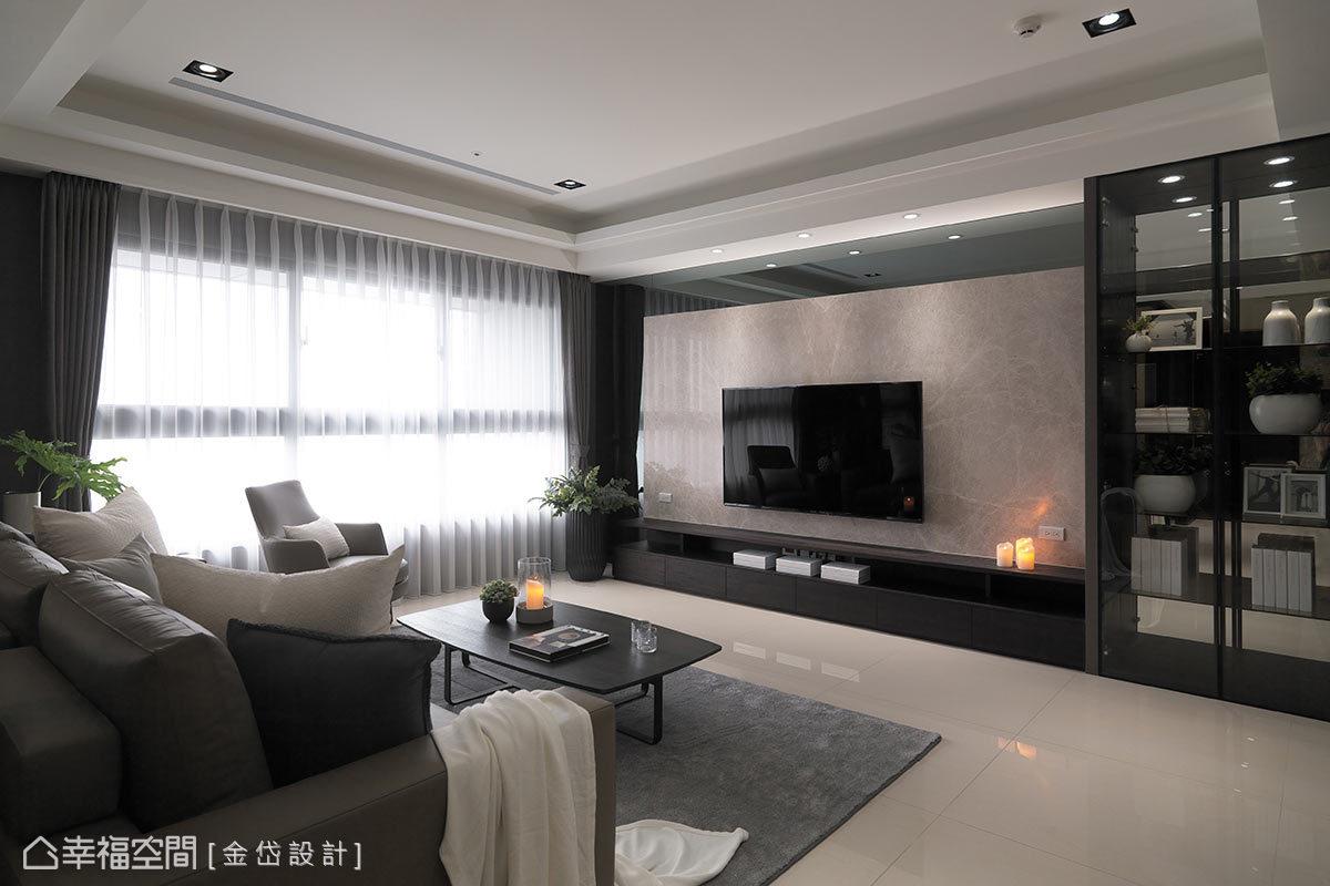 設計師陳美貴於電視牆的表現上,運用天然大理石、灰鏡及深色木皮,搭配右側的紅酒櫃,締造大器風範與實用機能。