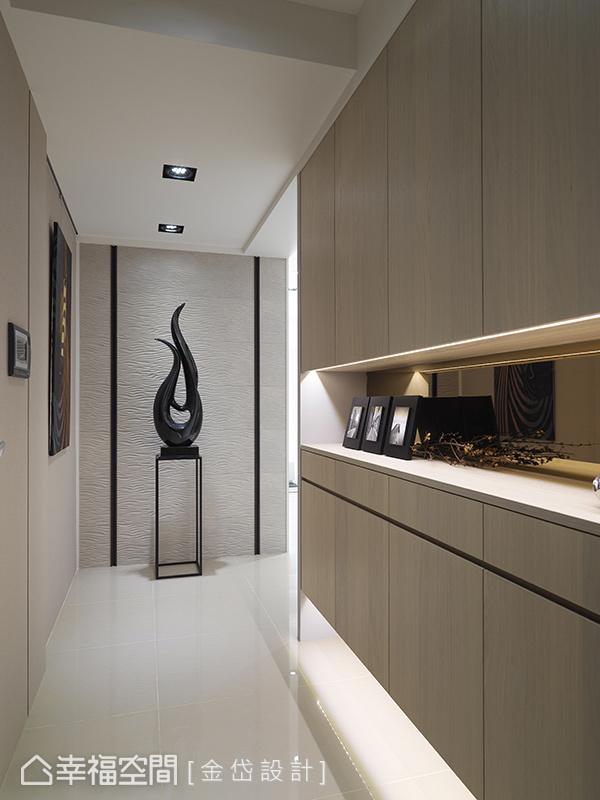 入門之後,玄關區右側以上下櫃及鏡面處理,下方則以騰空的方式營造輕盈感。