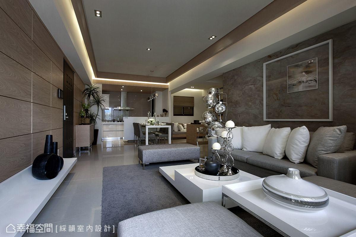 天花板以木質元素與間接照明,框塑出客廳與餐廳場域,讓視覺得以延伸,達成空間放大的效果。