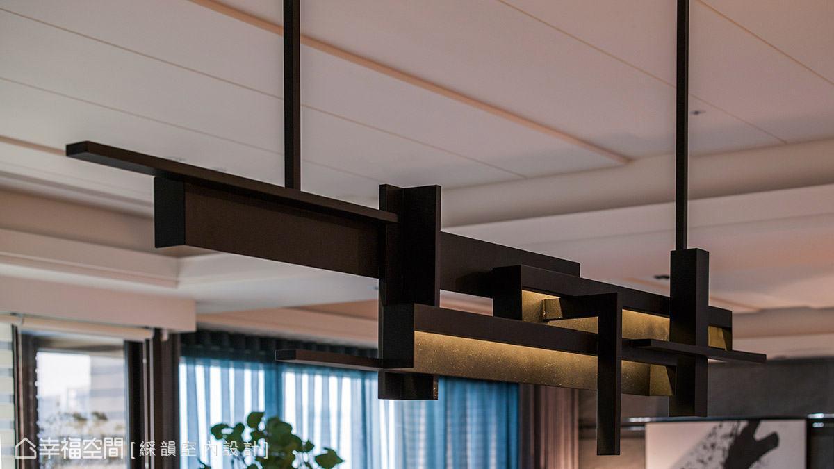 吳金鳳與范志聖設計師特別訂製金屬造型燈具,其切割線條亦延續自壁面與書櫃的線條,讓整體設計元素有所呼應。
