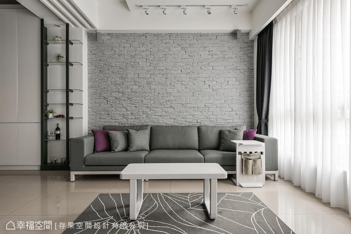 沙發背牆使用帶點粗獷的灰色文化石,搭配灰色軟件沙發,展現穩重的設計氛圍。