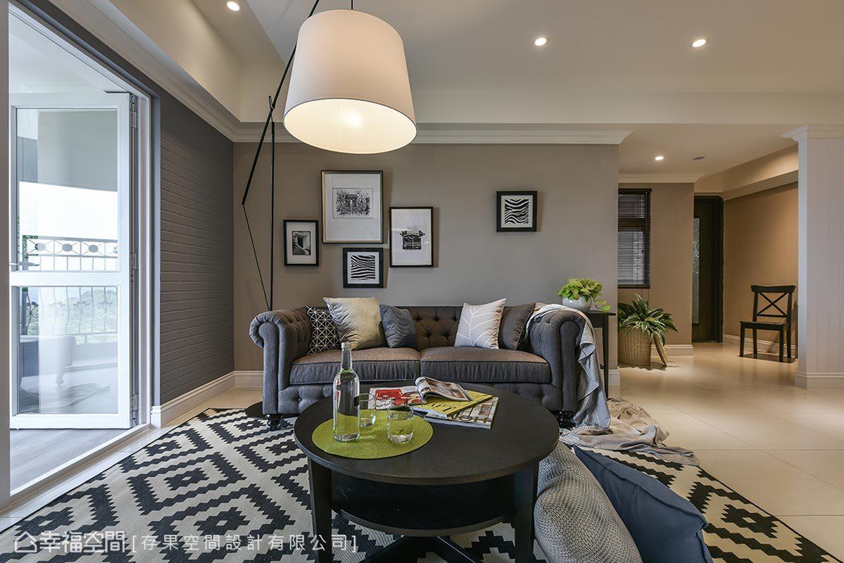 暖灰色為基底的沙發背牆,透過黑白相框作妝點,搭配簡約俐落的家具家飾,為空間挹注生活暖度。