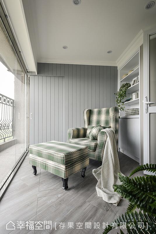以通透的玻璃打造,形成愜意的角落,架高的木地板下方規劃收納量體,透過灰色造型牆面隱藏通往洗衣間的入口動線。