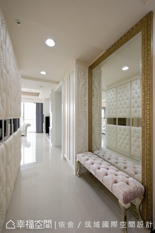 狹長型玄關走道,透過落地鏡放大空間感。櫃子側面以雕刻飾板美化,在鏡子的反射下彰顯其華美線條。