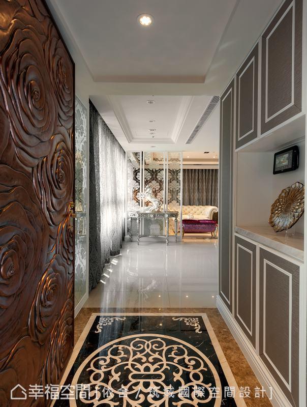 從玄關入內,敞朗大器的豪邸意象映入眼簾,地坪以黑、白、棕色的古典藤蔓圖騰,搭配上以白線條勾勒的繃布展示櫃,盡顯華麗典雅的風韻。
