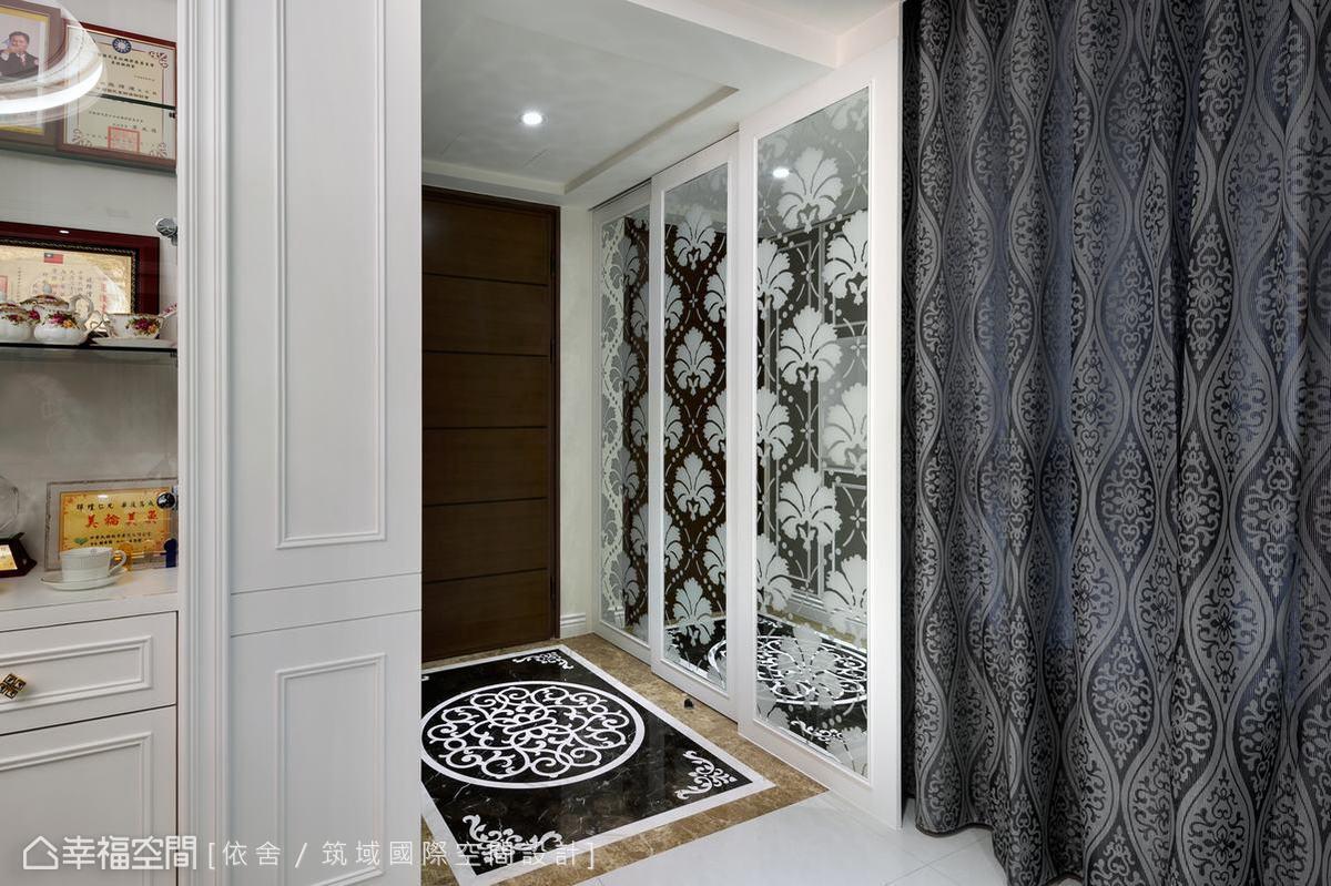玄關的左側並使用花草圖騰的鏡面增添場域的華美,而藤蔓圖騰地坪及俐落的線條搭配收納櫃繃皮,營造濃濃新古典的氛圍。