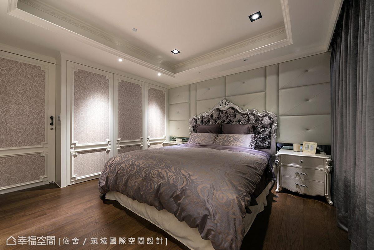有別於公共空間的色調,走入主臥房即可感受到淡淡紫色的柔和氛圍。床頭經典的繃皮設計,讓收納櫃完美藏身古典造型中,體現大器完整的主牆面。