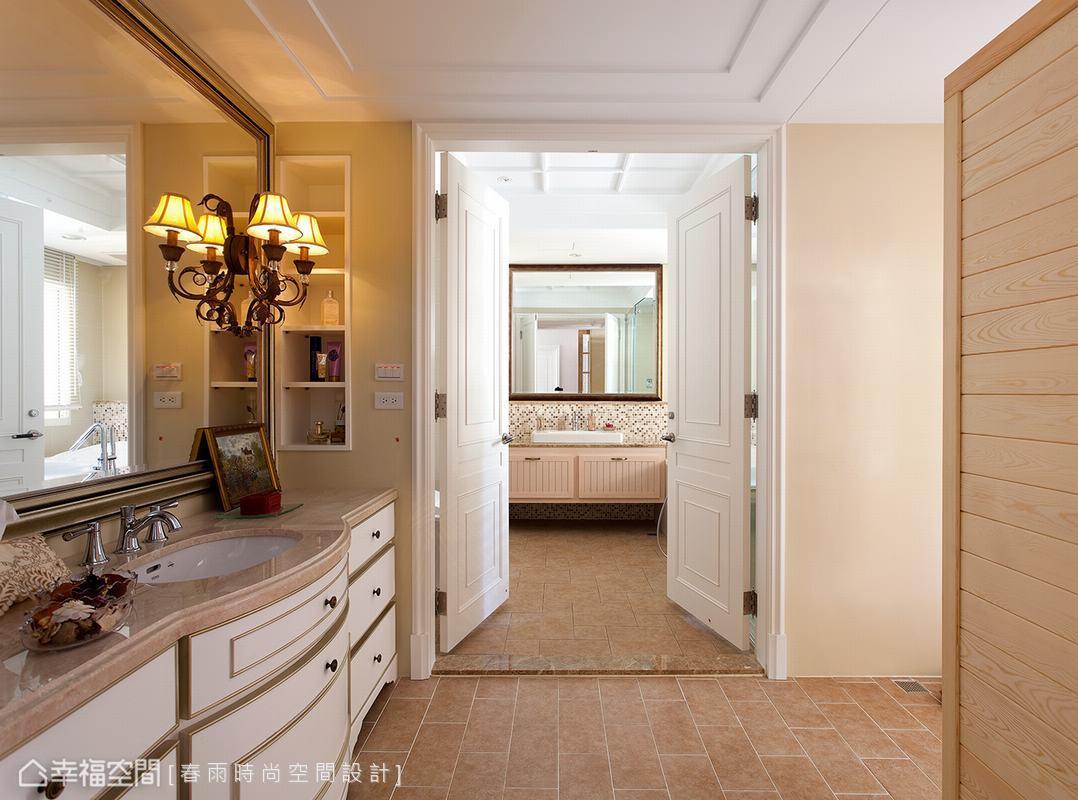 以畫框包覆超大鏡面,並將古典壁燈直接懸掛於鏡面上,克服鏡面易碎的作業難度後,光鏡面空間就隱隱呈現皇家古典氣質,天然大理石檯面下的浴櫃以木坐施以白色烤漆,再加上手工特調金漆描繪古典線條邊框,再復古地磚的搭襯下,延續客廳空間的英式古典優雅。