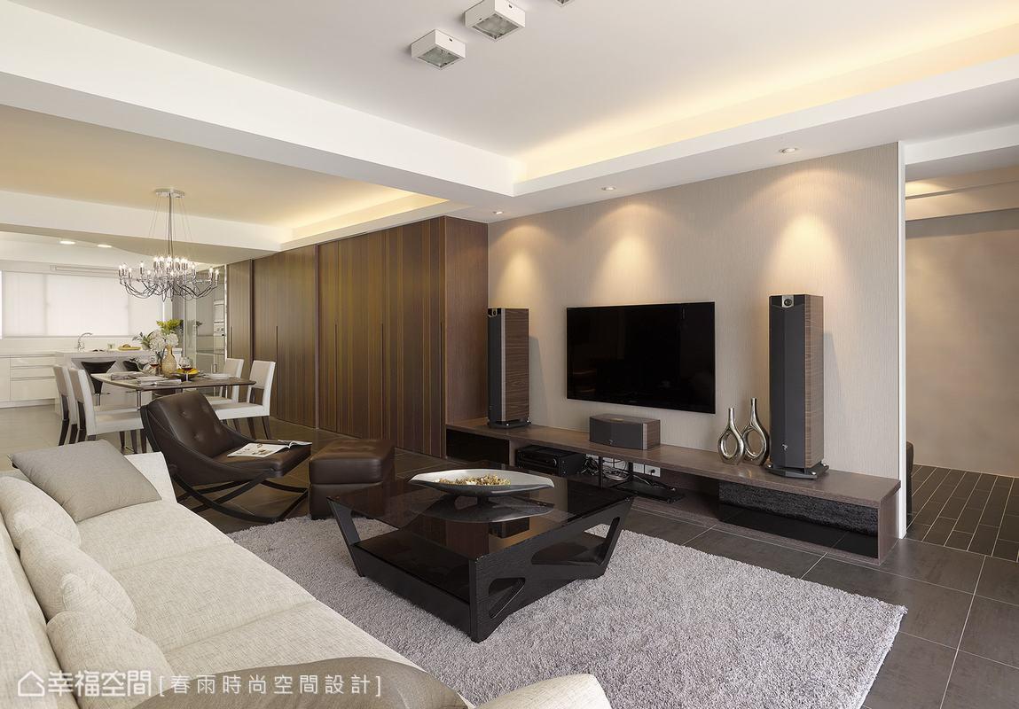 設計師以深色地坪搭配淺灰色訂製傢俱營造休閒穩重氛圍,而電視牆尺度正巧是後方玄關櫃體的長度,精算過比例的設計微調出平衡的生活樣貌。