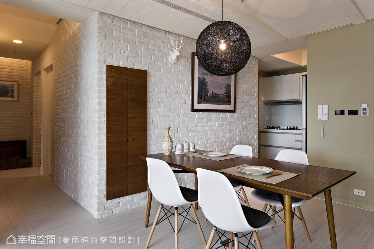 設計師利用樑下牆體厚度內嵌餐櫃,僅露出木色門片與飾品、掛畫共同織構餐廳主牆風景。