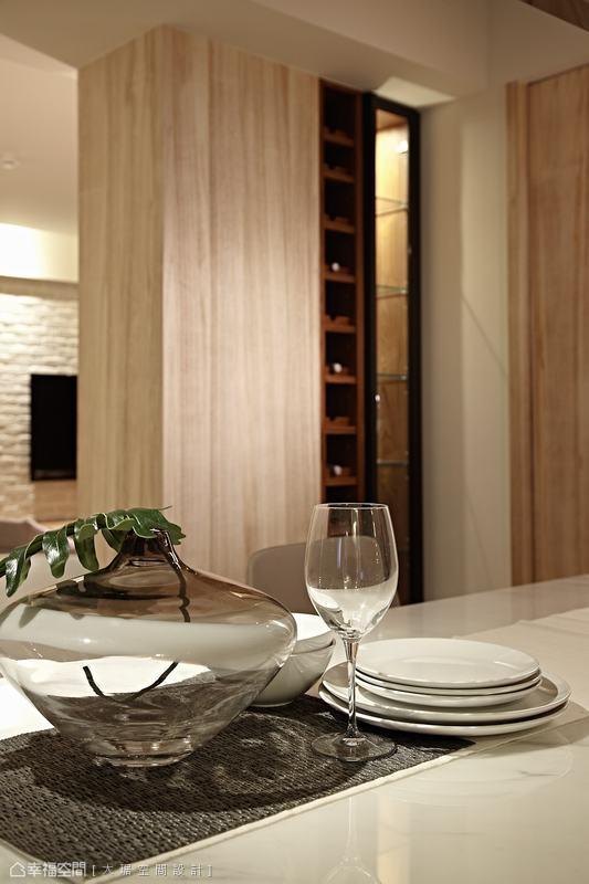 沙發背牆延展不僅遮掩後方衛浴入口、界定了場域獨立性,小酒櫃的運用而生更顯生活時尚度。
