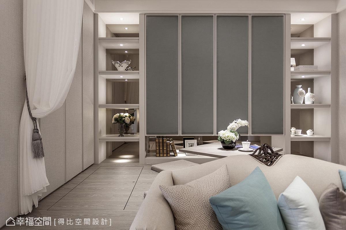 展示櫃鑲嵌灰鏡帶來折射效果,創造出空間深度;左側米灰色線條切割立面,以三道假門片帶來雙面櫃功能。
