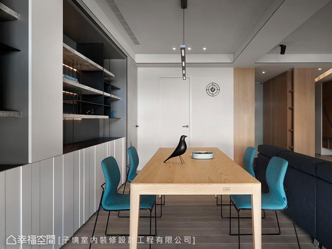 子境設計於餐廳擺設木質長桌搭佐藍綠色座椅,為用餐空間營造簡約溫馨感受。