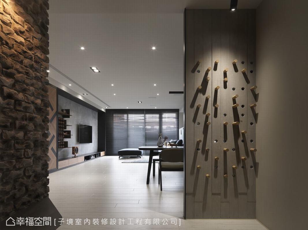玄關右側的水泥色屏風看似一道藝術裝置,實則是利用孔芯和可調式木桿創造有趣的牆面收納。