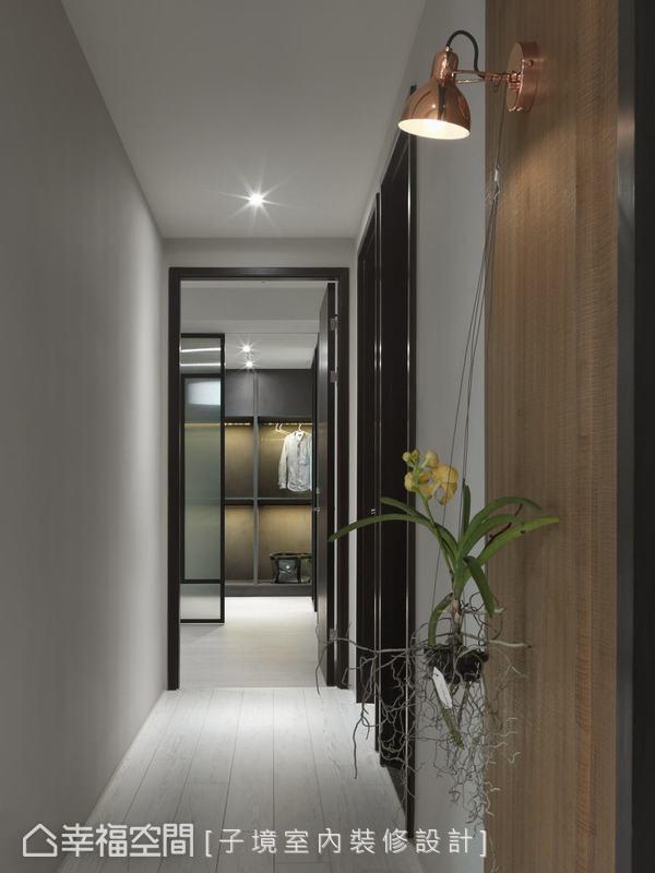 除了將公共空間的水平長軸徹底呈現,通往臥房的廊道以白色處理,突顯了廊道盡頭的黑色框架線條,延伸公領域的視覺穿透性。