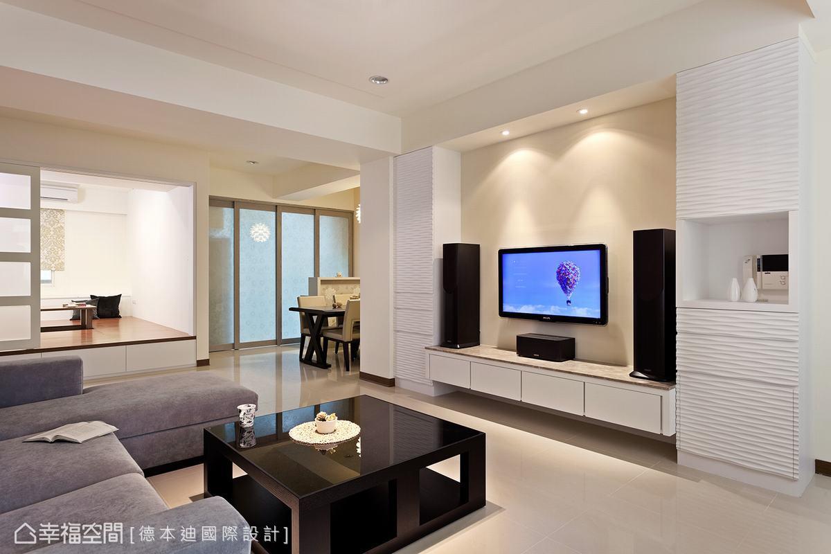 設計師保留對向電視主牆的乾淨度,僅以象牙白漆面表現淨白優雅,一旁再以亂紋板及烤漆設計對稱收納櫃體,藉由立體的紋路與沙發背牆的紋理互為呼應。