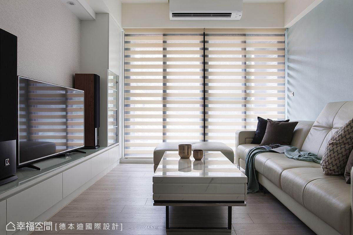 窗外的陽光經由大面窗進入室內,與粉藍色的沙發背牆、超耐磨木底板組合,形塑空間的暖度。