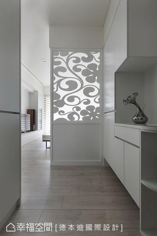 用雕花板及櫃體規劃出玄關區域,而透光的雕花板不但保有穿透感又同時兼具風水考量,避開屋主在意的穿堂煞。