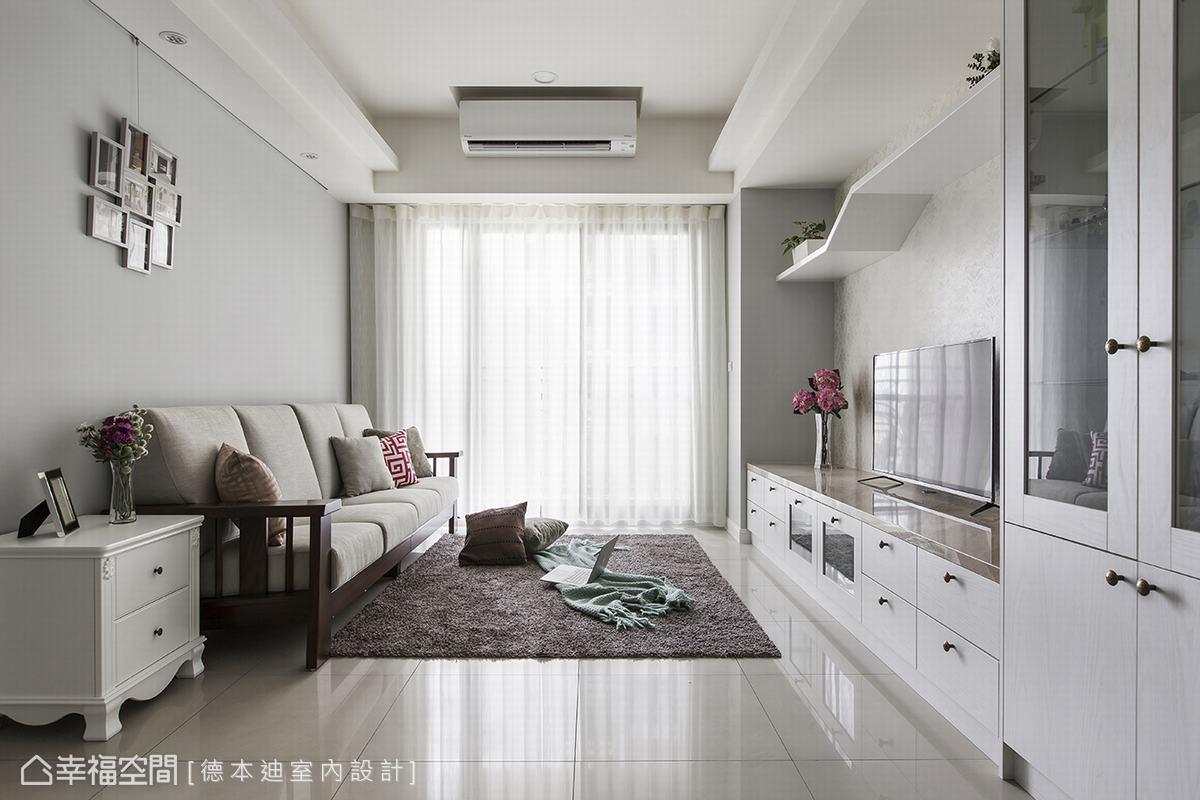 以白色櫃體和灰藍色沙發背牆所圍繞的客廳空間,色調清新、沈穩。在自然光線撒下的同時更涵養空間中的暖意。