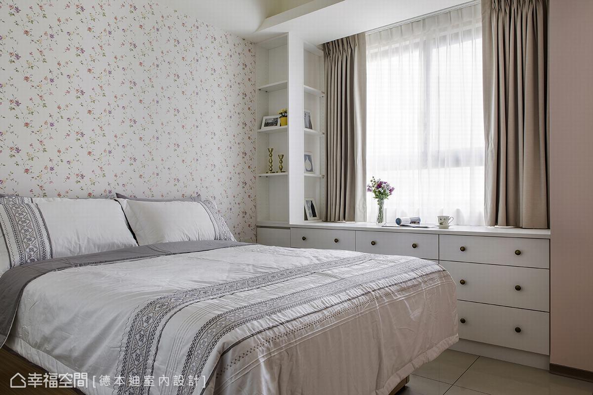 在床頭牆面飾以小碎花壁紙,顯現優雅氣息。為了建置完整展示機能,也利用寬敞壁面設計出獨具風格的雙面櫃。