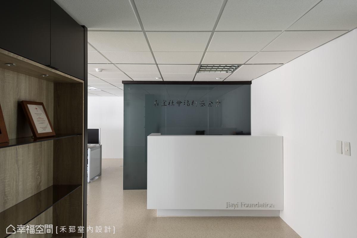 以灰玻璃大面噴砂的效果,突顯透亮的基金會名稱;而結合比例與堆疊概念的白色櫃台,俐落地呈現出銀白色LOGO,塑造簡潔時尚的印象。