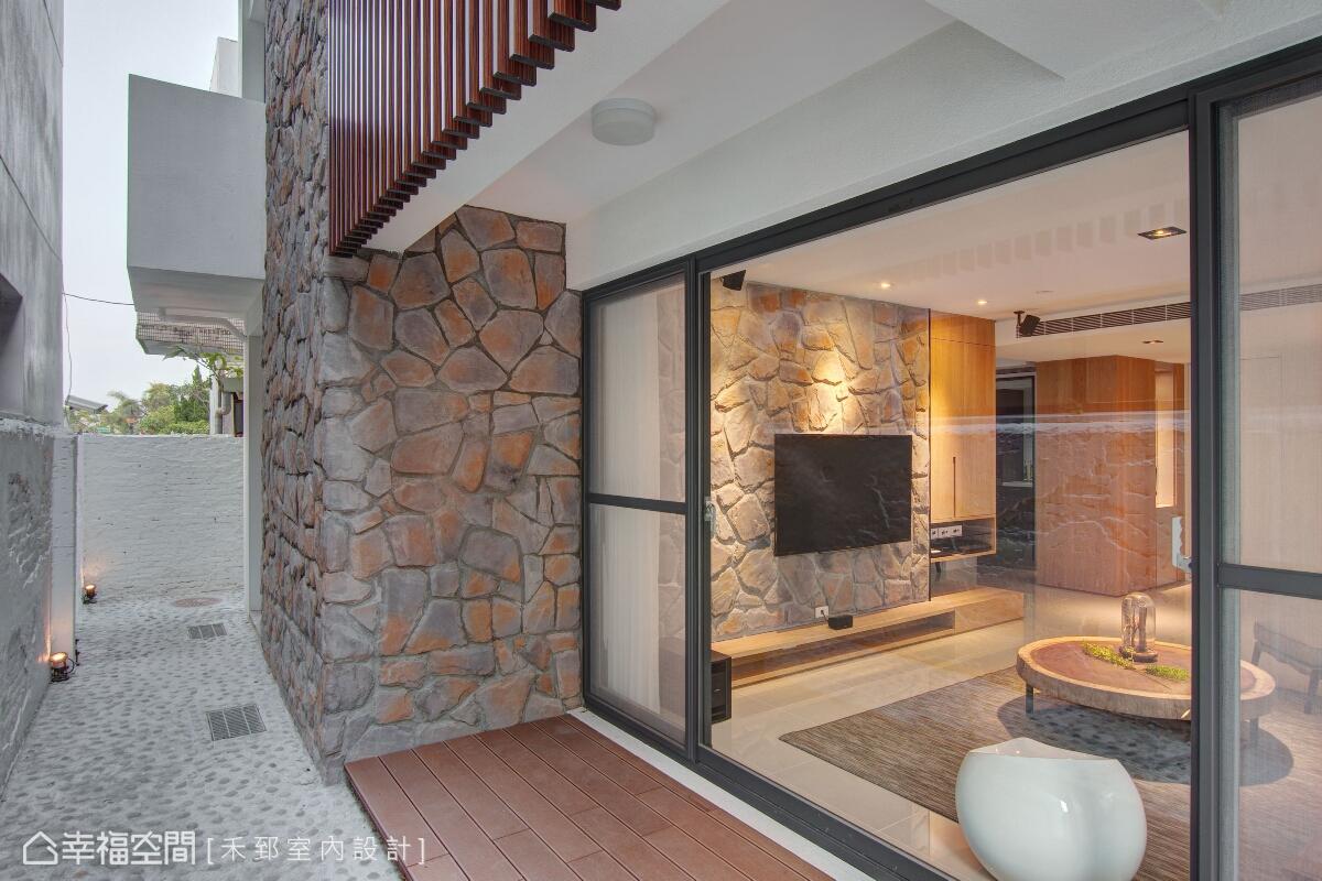 禾郅室內設計以亂石造型的文化石來鋪述電視牆,並由內延伸至戶外牆面,引發人與窗外的自由對話。