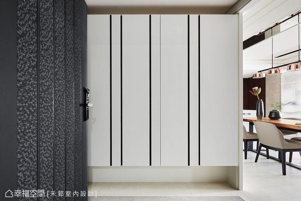 白色鞋櫃採用隱藏門設計,結合溝縫手法拉出疏密有致的線條,帶來簡約俐落的現代風格感受。