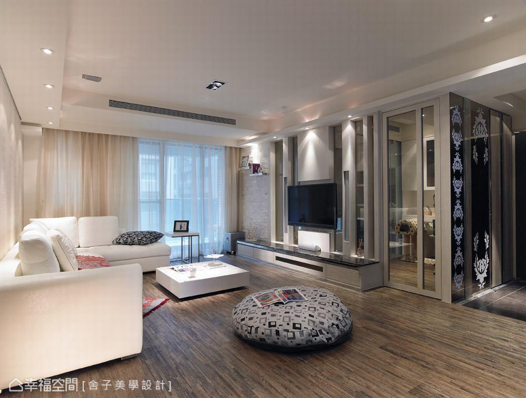 客廳場域,設計師捨棄建商原配置的拋光石英磚,改以飛天斑馬紋木板構築滿室溫馨。