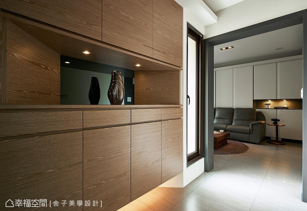詹秉縈設計師在木作鞋櫃的中央搭配展示平台與亮面質材,形塑一處優雅的藝術端景。