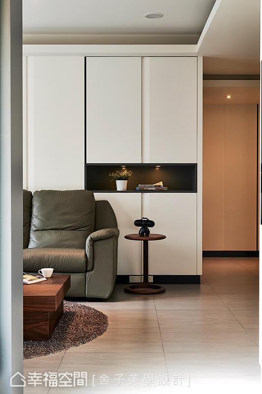 沙發後方裝置整面收納櫃,外側櫃體的中央以鑿空呈現,並內嵌間接光源,創造展示機能。