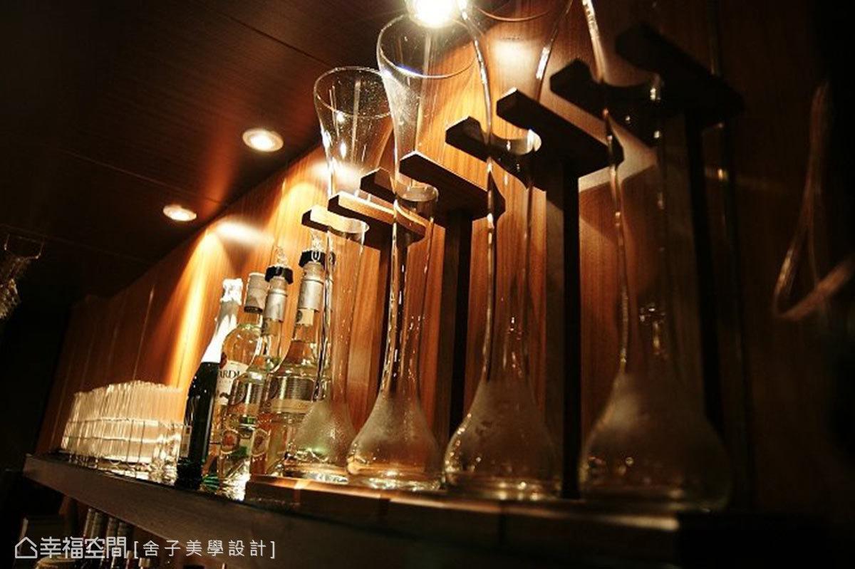 展示層板上放置著酒杯與名酒,藉由光線與材質的運用,鋪述出沉穩內斂的質感。