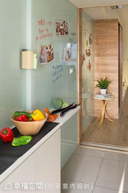 轉入餐廚空間,廚房的牆面利用烤漆玻璃,可以在此塗鴉留言;另外,逃生門也以隱藏的方式的構置於此。