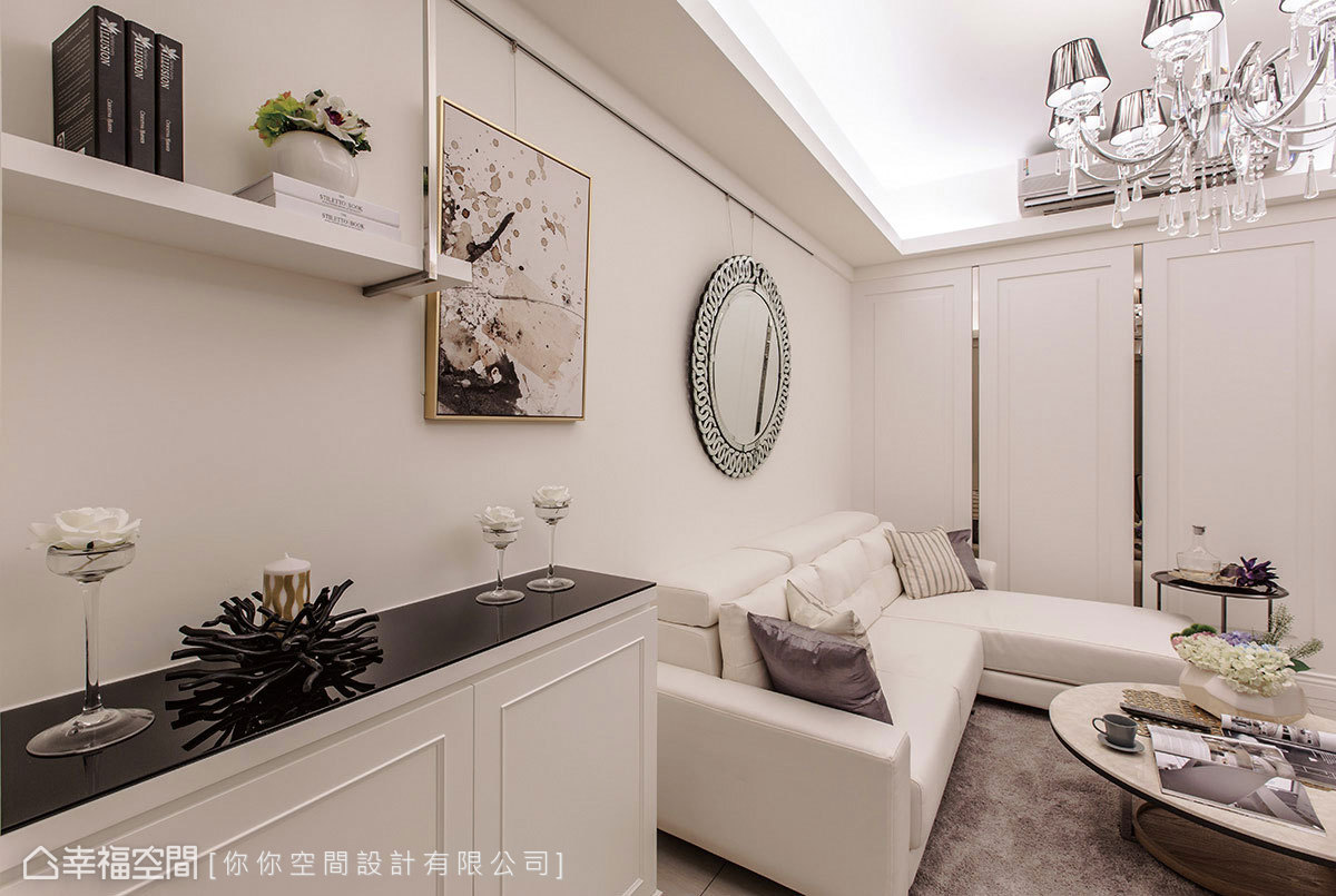 沙發牆上裝置吊畫軌道,串連起特殊造型的鏡子與畫作,與一旁的展示空間共同營造出柔美氛圍。