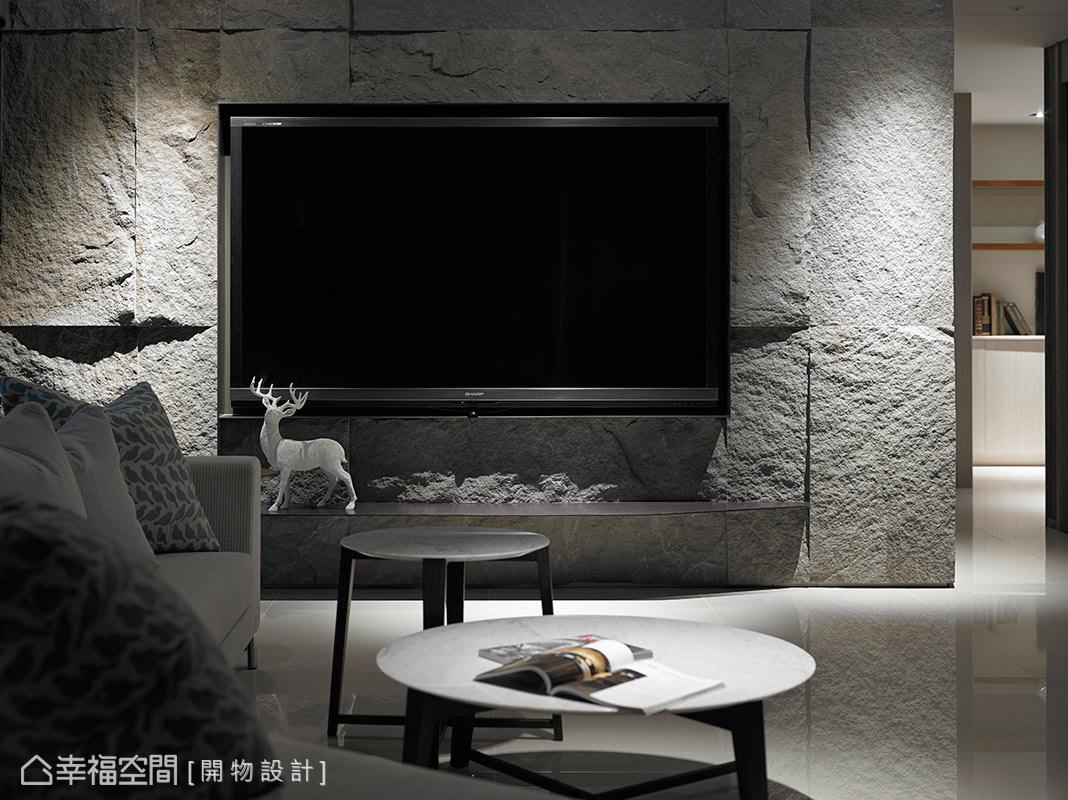 設計師楊竣淞與羅尤呈運用粗獷肌理的石皮,作為電視主牆的立面表現,圍塑恢弘大器的面貌。