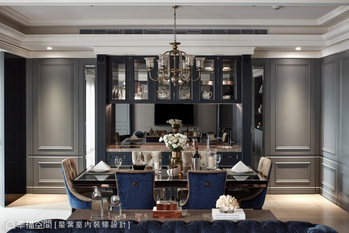 為了和彼端的電視牆達到對稱效果,餐廳便成為此空間的視覺焦點。綜合兩屋主的喜好,採鐵灰色、灰鏡以及大理石檯面等素材打造餐檯,並在櫃體邊框角落以雕花裝飾,打造兼具設計美感和實用機能的餐櫃兼餐檯。
