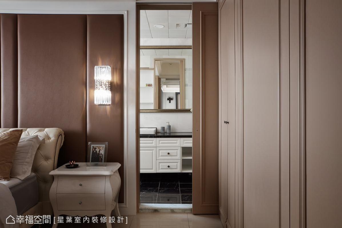 與深色調的公共空間不同,主臥室改以舒緩心情的暖色系做為主色。後方更衣室櫃體則以系統櫃設置,並以木作線板修飾櫃間,再加上灰玻,更提升質感。