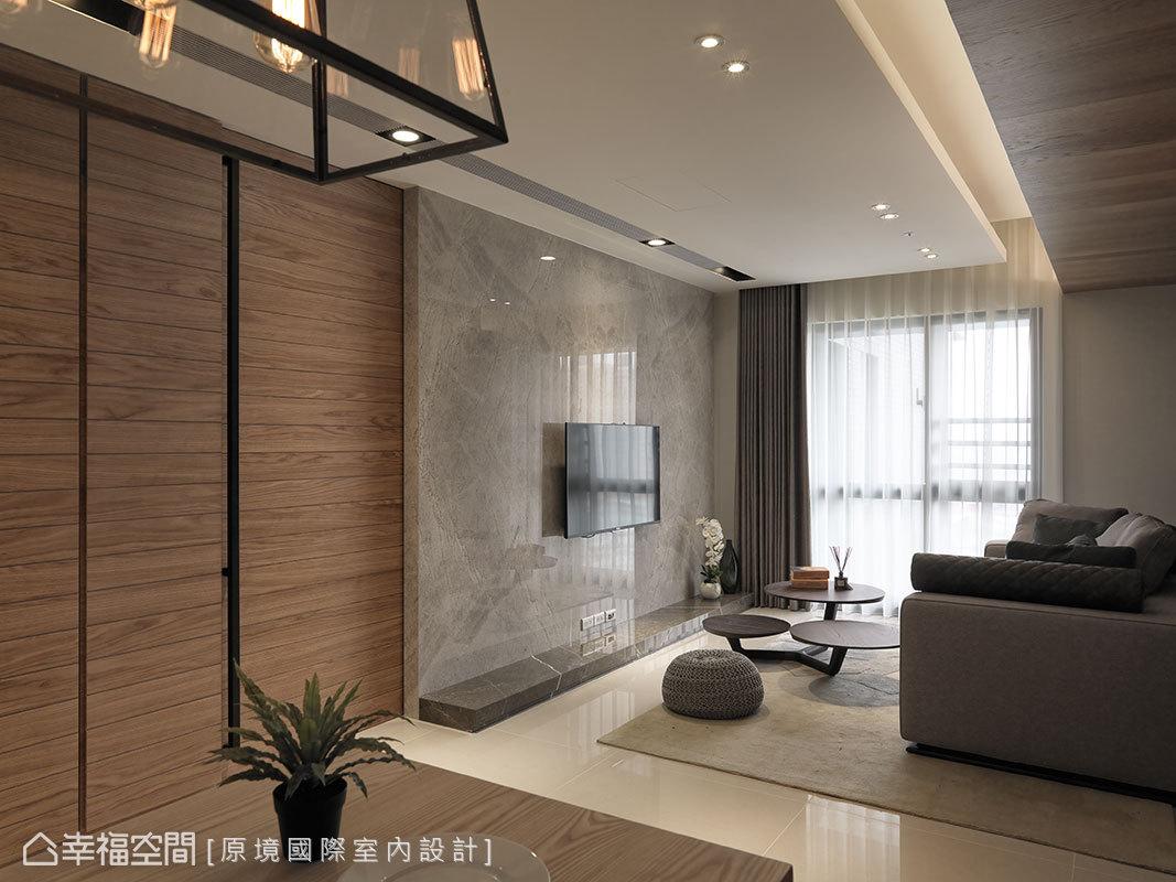 將廚房的入口移位後,以溫潤的木皮門片,淡化入口動線,並延展出一道大理石電視主牆,形成木石共舞的景致。