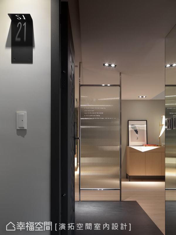 藉由牆面的投影巧思替住宅揭開序幕,一面長虹玻璃取代了傳統玄關隔屏,文字標語淡淡地道出了屬於這個家的生活哲學。