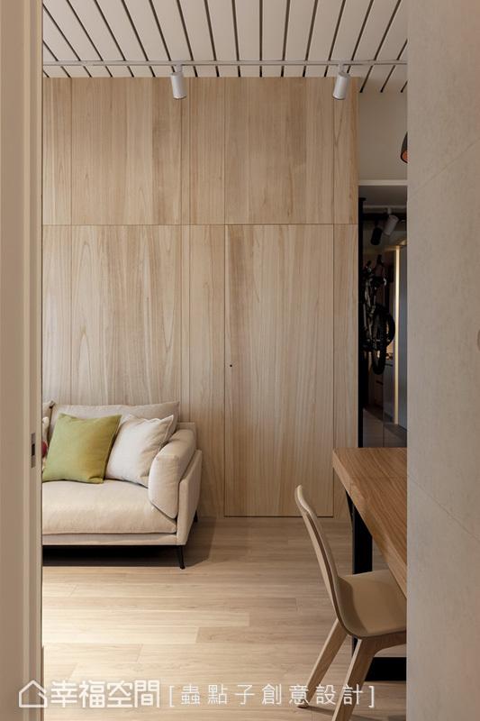 鋪貼實木皮形成不規則的線性分隔造型,結合暗門設計淡化主臥入口門片,維持立面完整度。